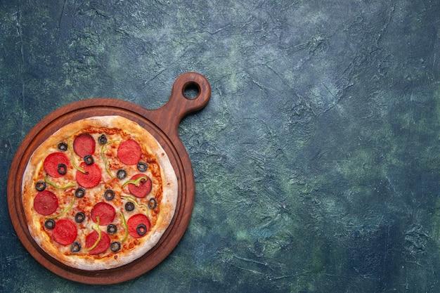 空きスペースのあるダークブルーの表面の右側にある木製のまな板においしいピザ