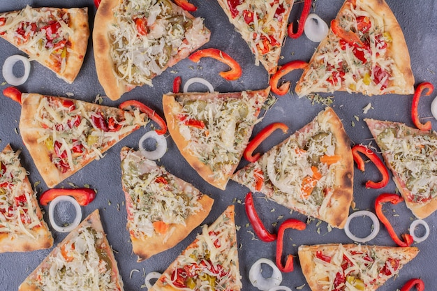 Tasty pizza slices on blue with onion rings and pepper.
