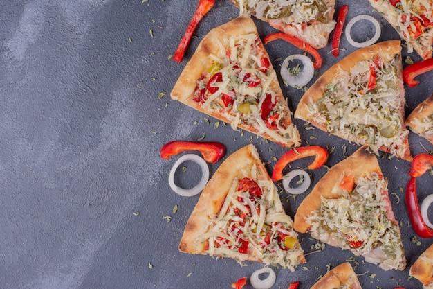 オニオンリングとコショウを添えた青のおいしいピザスライス。