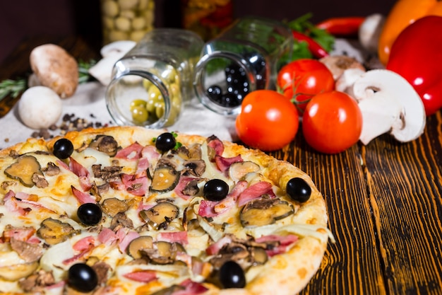 Tasty pizza with black olives on wooden table, tomatoes, mushrooms and other vegetables