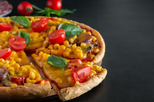 Tasty pizza with cherry tomatoes and sliced slice on a black background