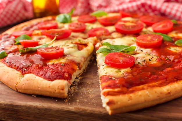Tasty pizza with cut slice on chopping board
