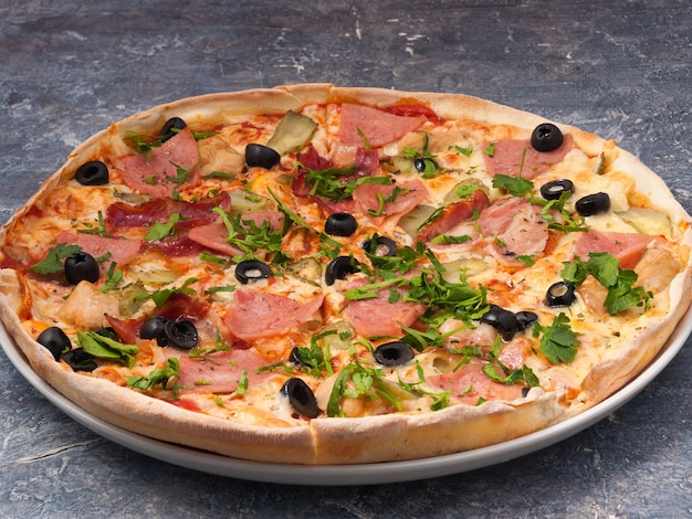 Tasty pizza with ham chicken bacon mozzarella cheese and olives