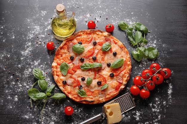 暗いテーブルに食材を使ったおいしいピザ