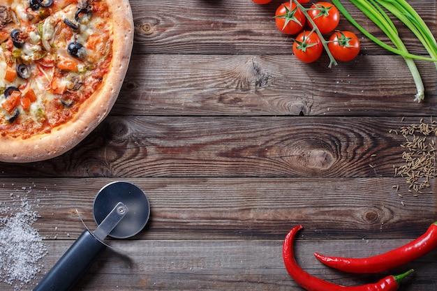 나무 판자에 재료를 넣은 맛있는 피자. 중앙에 빈 공간이 있는 상위 뷰