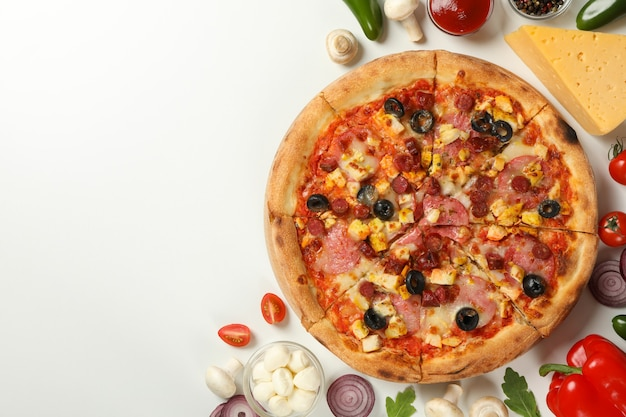 Tasty pizza with meat and ingredients on white