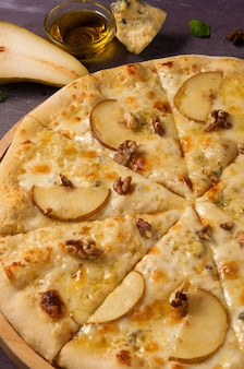 Tasty pizza with pear and gorgonzola on a wooden board close up