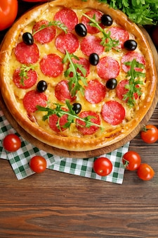 Tasty pizza with salami on decorated wooden table