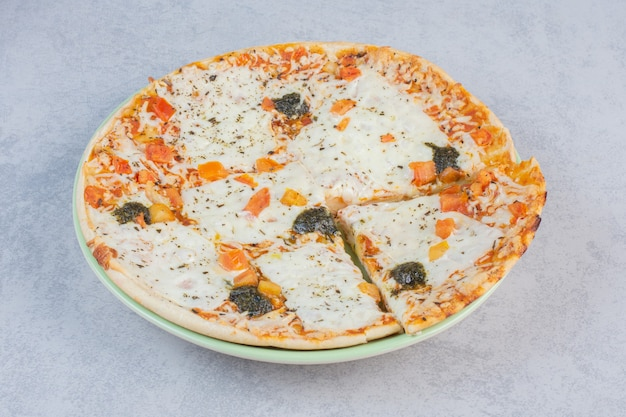 Tasty pizza with salted cucumbers and cheese on a white background.