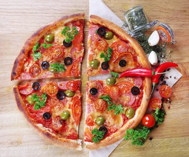 나무 테이블 배경에 소시지, 야채, 칠리 페퍼를 곁들인 맛있는 피자