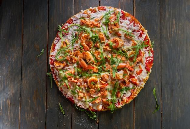 エビとルッコラの木製のテーブルのおいしいピザ。上面図。