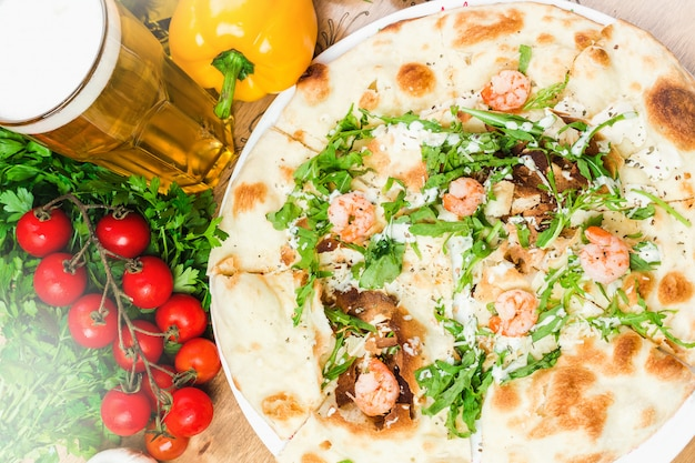 Tasty pizza with shrimp and arugula close up