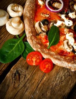 Вкусная пицца с помидорами и зеленью на деревянной доске.