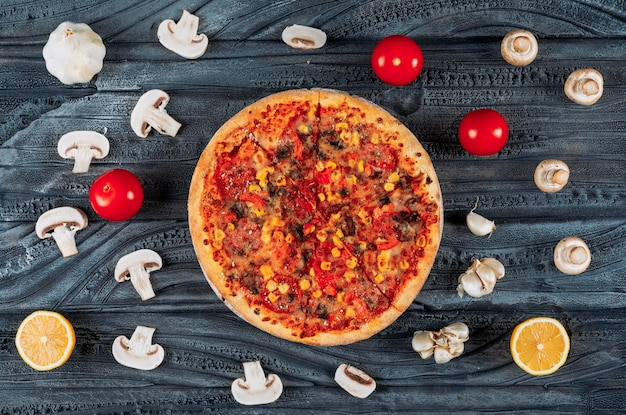 Tasty pizza with tomatoes, a lemon, garlic and mushrooms top view on a dark wooden background