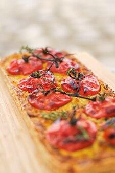 Вкусная пицца с помидорами на разделочной доске