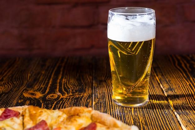 グラスビールの近くの木製テーブルにさまざまなトッピングとチーズが入ったおいしいピザ