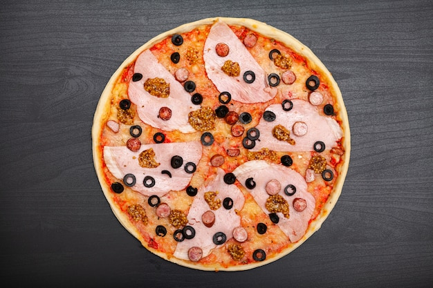 Tasty pizza with various flavored ingredients on dark