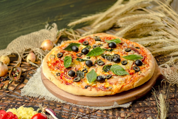 Tasty pizza with vegetables and basil