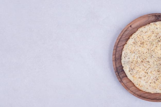 Gustosa pizza sul piatto di legno sulla superficie bianca