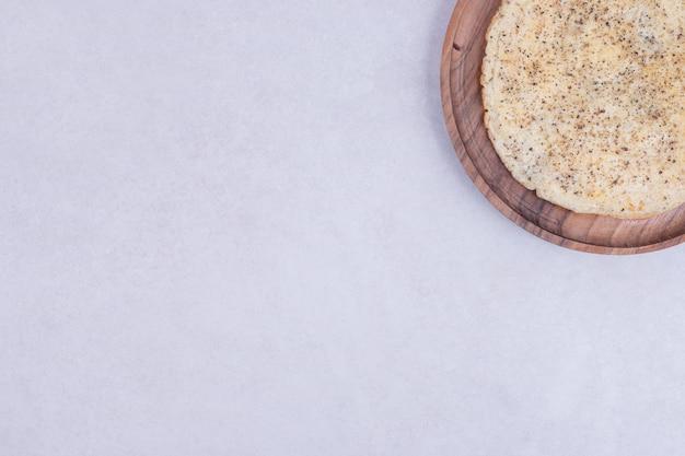 Gustosa pizza sul piatto di legno su bianco
