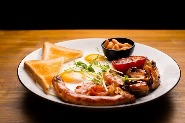 Вкусная тарелка британского завтрака с яичными сосисками и тостами