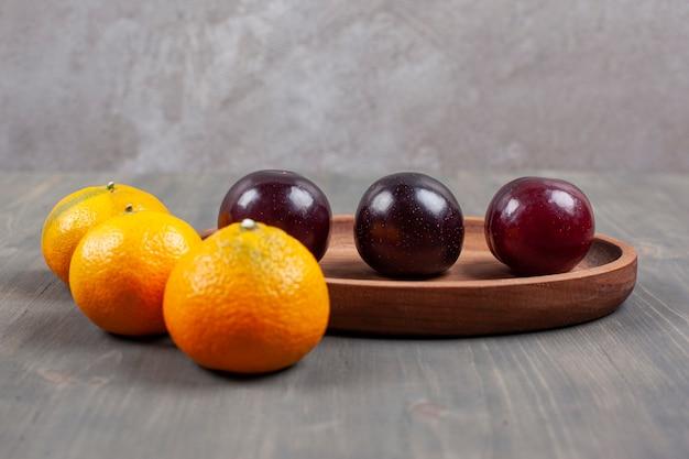 Вкусные сливы с восхитительными мандаринами на деревянной тарелке. фото высокого качества