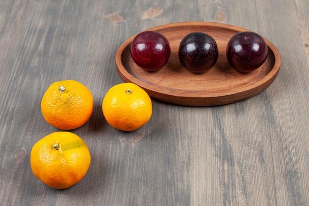 나무 테이블에 맛있는 감귤과 맛있는 자 두. 고품질 사진