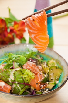 Tasty poke with salmon and vegetables close up