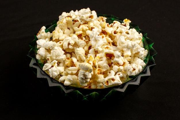 Tasty popcorn bright yummy salted inside round plate on a dark