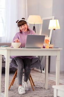 Вкусный попкорн. очаровательная девушка держит улыбку на лице, глядя на экран своего компьютера