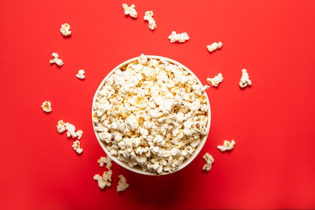 Tasty popcorn in a paper cup on a red background, top view