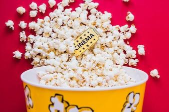 Tasty popcorn with cinema ticket