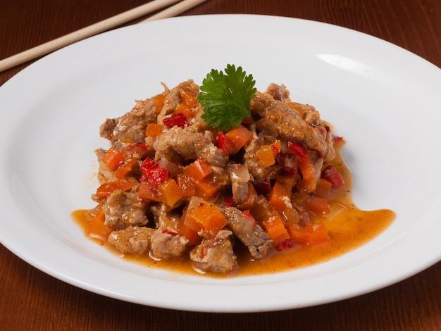 白いプレートにアジアンスタイルの甘酸っぱいソースでおいしい豚肉
