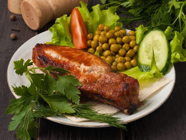 채소로 장식 된 그릴에서 구워진 뼈에 맛있는 돼지 등심