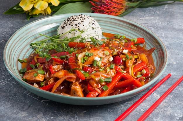 달콤한 소스에 야채와 쌀을 곁들인 맛있는 돼지 고기 아시아 요리