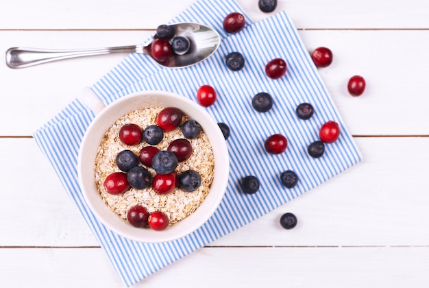 Porridge gustoso con frutta su tavola di legno