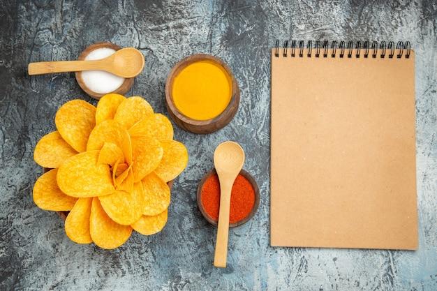 꽃처럼 장식 된 맛있는 감자 칩은 회색 테이블에 숟가락과 노트북으로 다른 향신료를 형성했습니다.