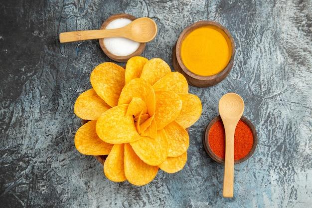 꽃처럼 장식 된 맛있는 감자 칩은 회색 배경에 숟가락으로 다른 향신료를 형성했습니다.