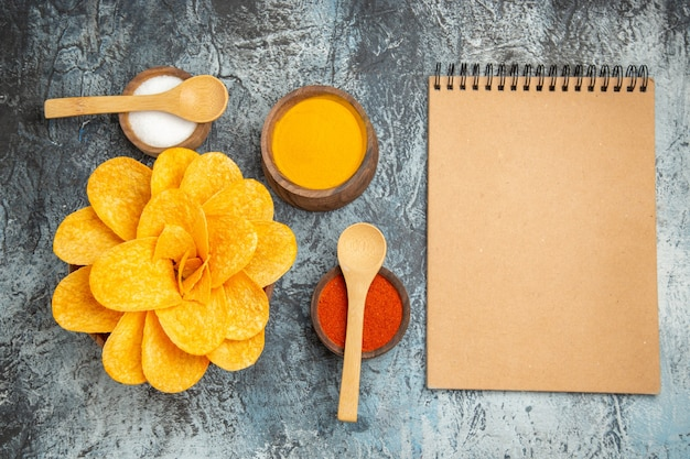 Tasty potato chips decorated like flower shaped different spices with spoons on them and notebook on gray table