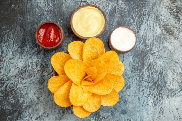 Tasty potato chips decorated like flower shaped and salt with ketchup mayonnaise on gray background