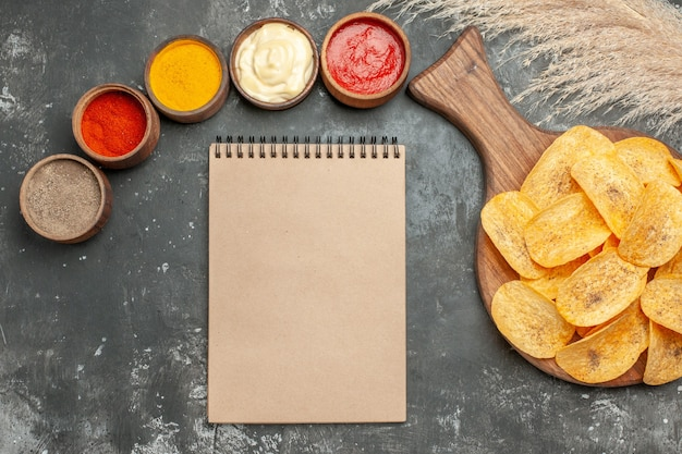 Tasty potato chips spices with ketchup and notebook on gray background