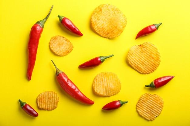 Вкусные картофельные чипсы с перцем чили на желтом