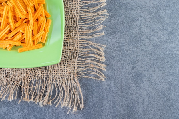 Вкусный картофель фри на тарелке на текстуре на мраморной поверхности
