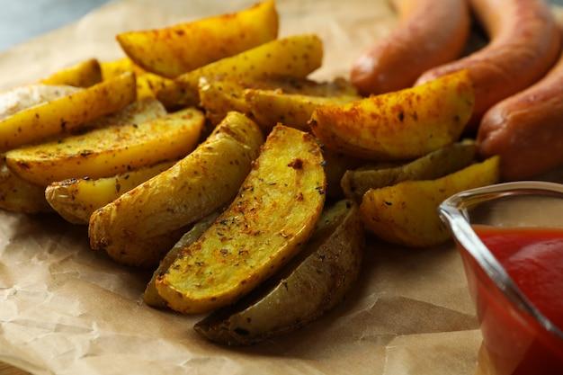 Tasty potato wedges, sauce and sausage, close up