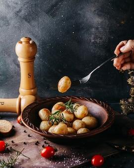 Gustose patate intere cotte salate e speziate intorno a pomodori rossi freschi sulla superficie scura