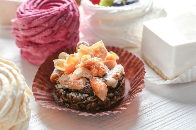 Tasty praline cake on wooden background