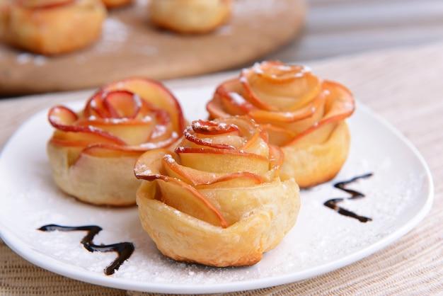 テーブルのクローズアップのプレートにリンゴの形をしたバラとおいしいパイ生地