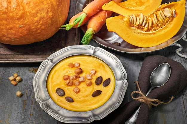 Tasty pumpkin and carrot cream soup served with croutons and pumpkin seeds in metal pewter bowl