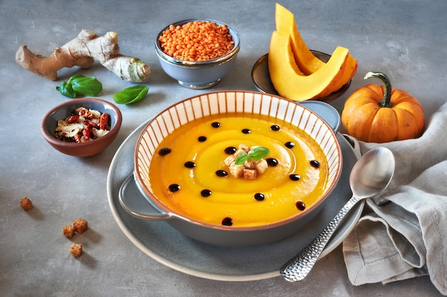 Tasty pumpkin cream soup served with croutons and balsamic vinegar in stripy ceramic plate
