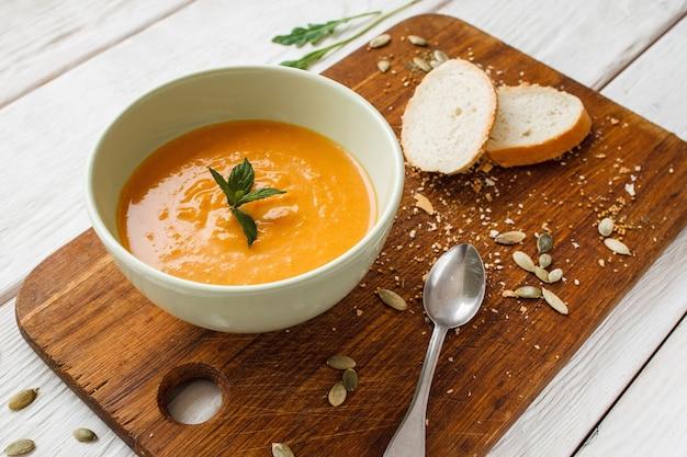おいしいカボチャのクリームスープ-パンとスプーン。木の板のボウルにオレンジ色のニンジンのお粥の上面図